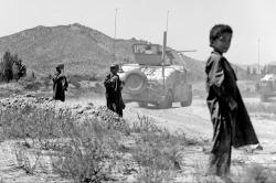 Afghani kids while a US patrol passes